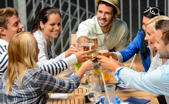 Group of cheerful people toasting with drinks